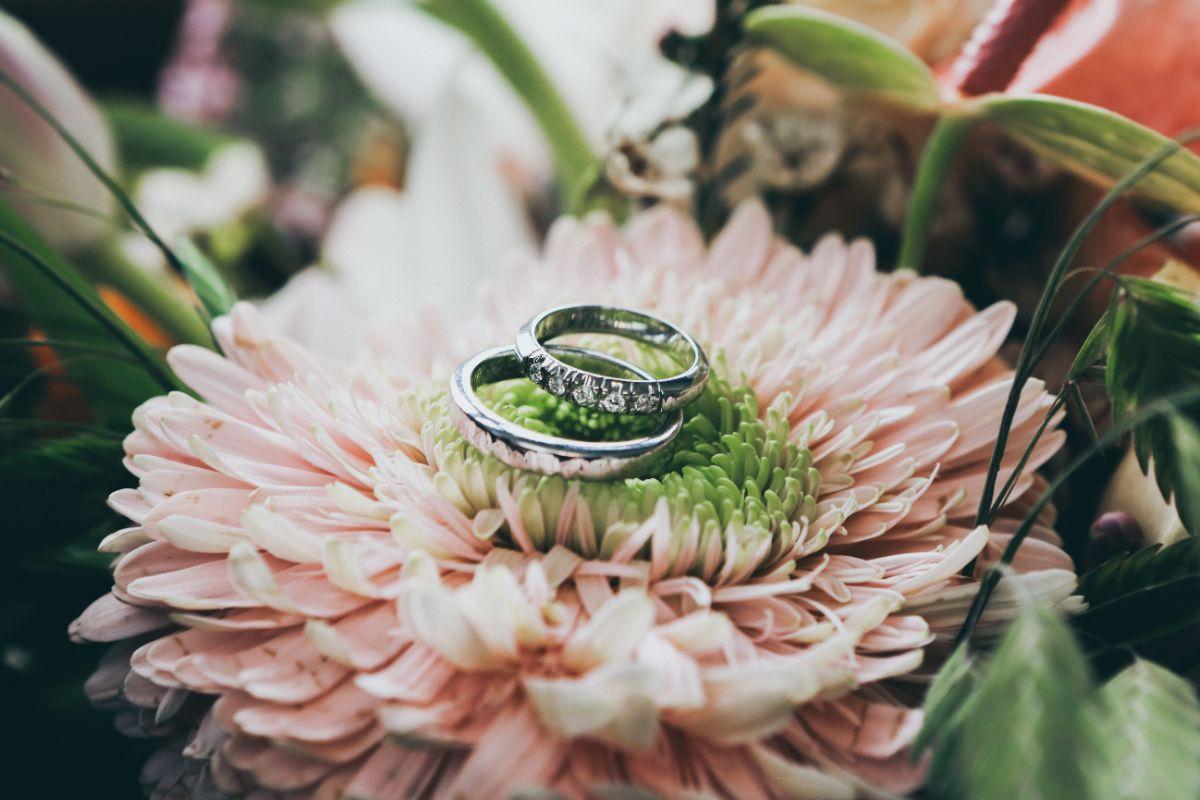 花の上にあるシルバーの結婚指輪